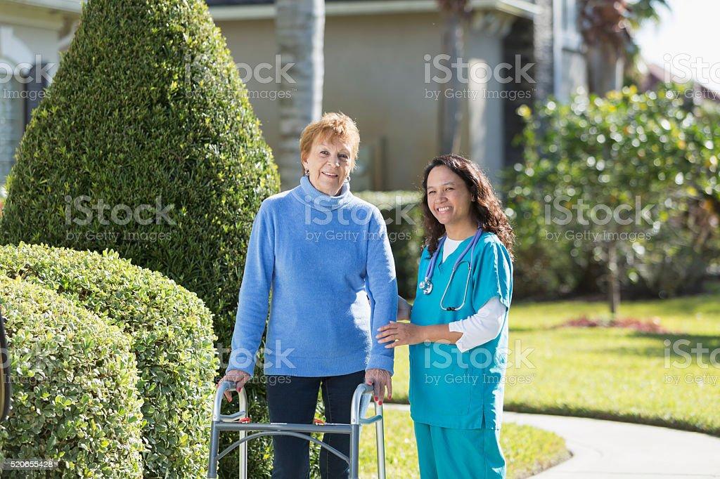 Nurse helping elderly woman using walker outdoors stock photo
