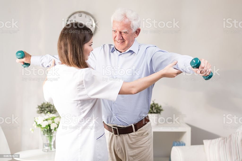 Nurse helping patient to exercise stock photo