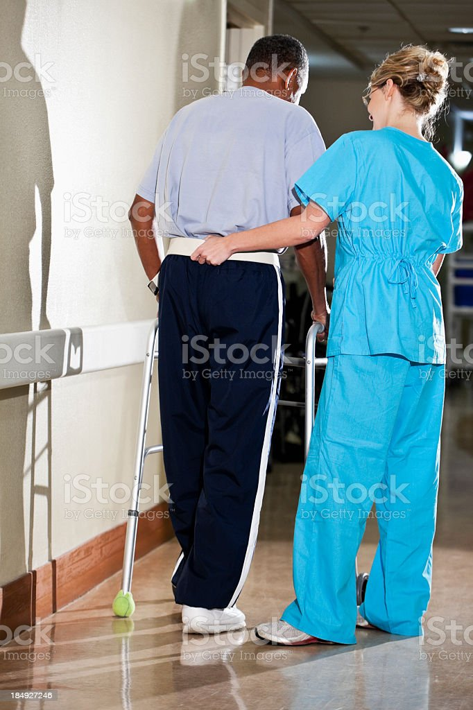 Nurse helping patient walk down hospital corridor royalty-free stock photo