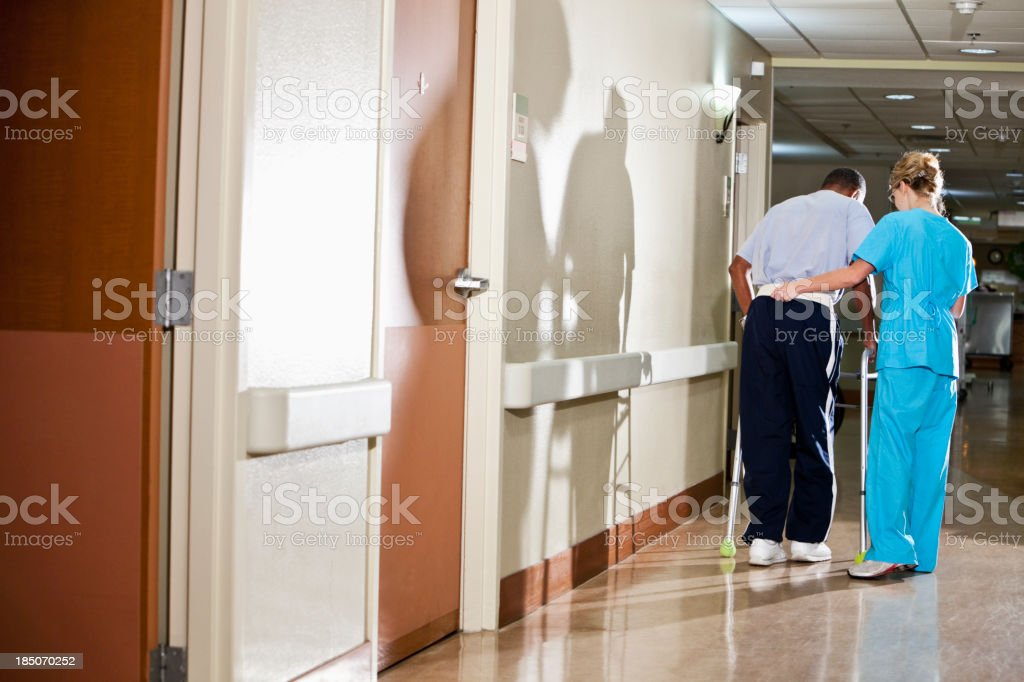 Nurse helping patient walk down hospital corridor stock photo
