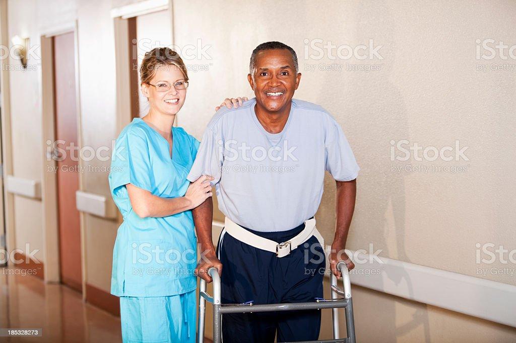 Nurse helping patient walk down hospital corridor stock photo