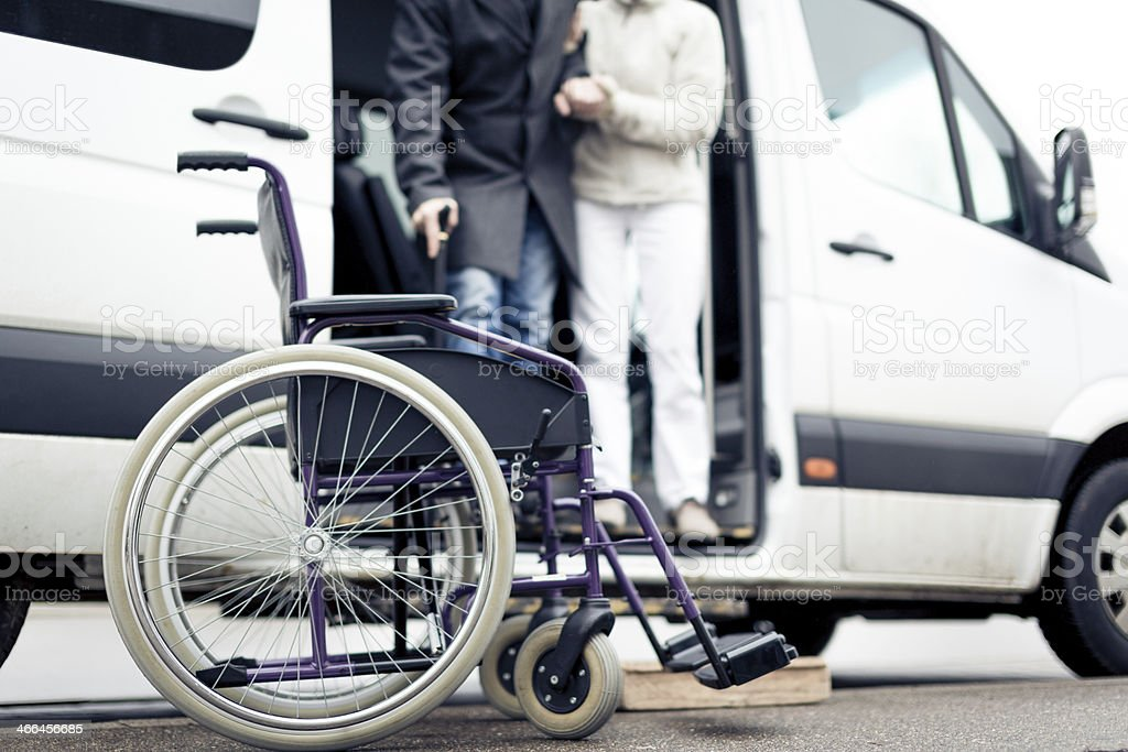 nurse helping senior man exit a van stock photo