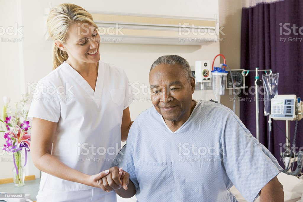 Nurse Helping Senior Man To Walk stock photo