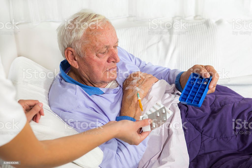 Nurse Helping Senior Man With Medication stock photo
