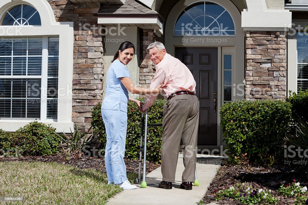 Nurse helping senior man with walker in front of house stock photo