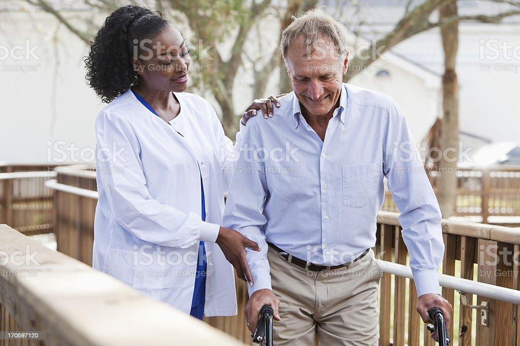 Nurse helping senior man with walker stock photo