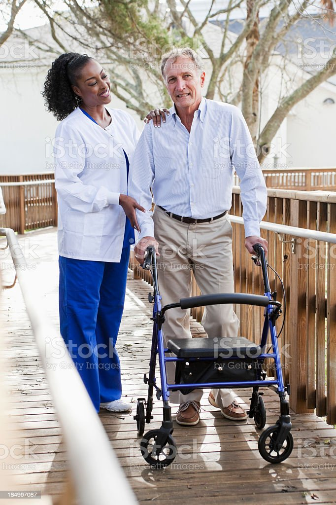 Nurse helping senior man with walker royalty-free stock photo