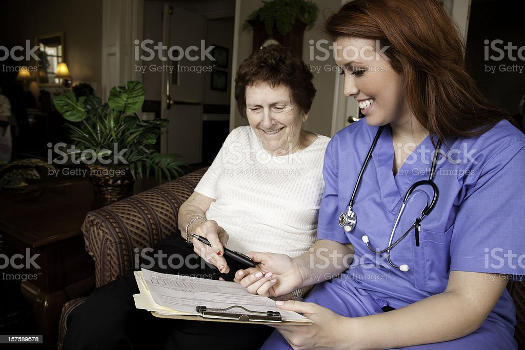 Nurse Helping Senior Woman Fill Out Medical Forms royalty-free stock photo