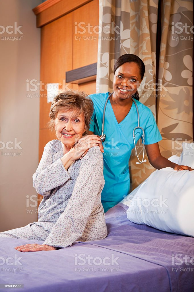 Nurse helping senior woman in hospital room stock photo