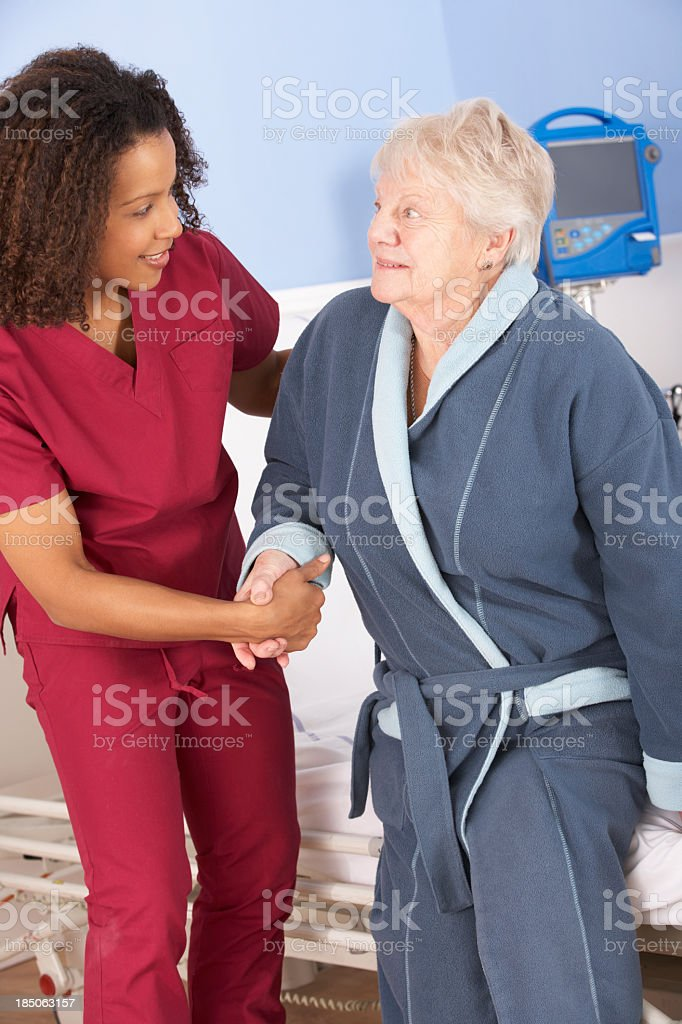 Nurse helping senior woman out of bed in hospital royalty-free stock photo