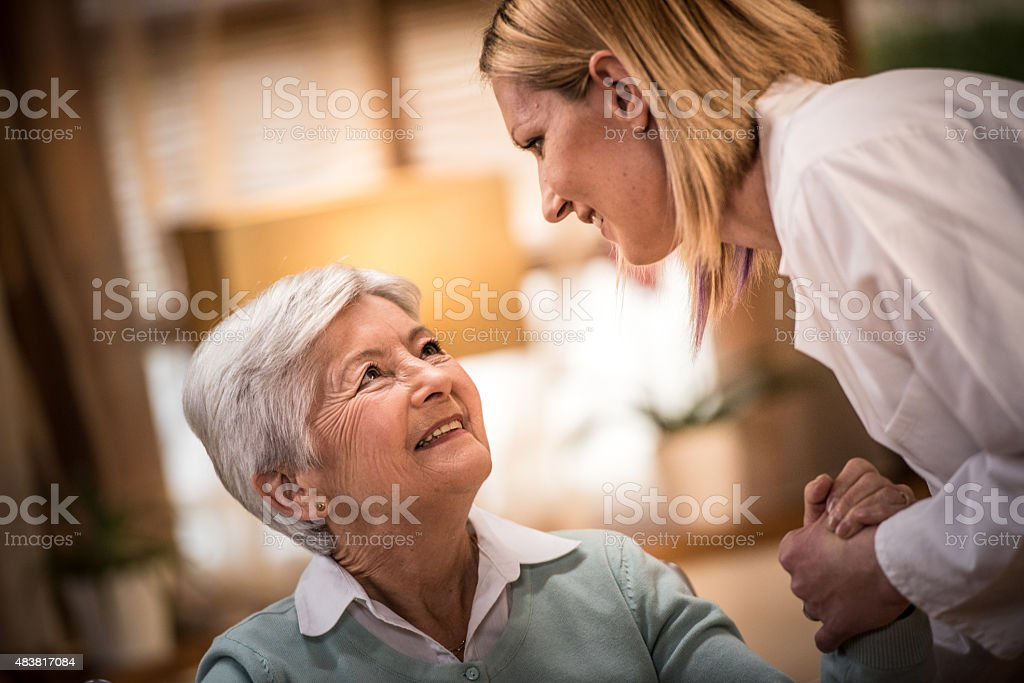 Nurse helping senior woman stock photo