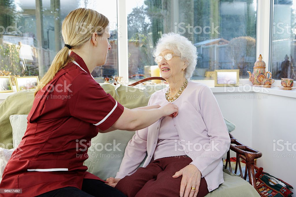 Nurse helping senior woman to dress in a care home royalty-free stock photo