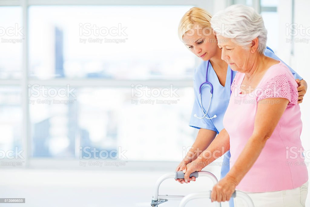 Nurse Helping Senior Woman With Walker stock photo