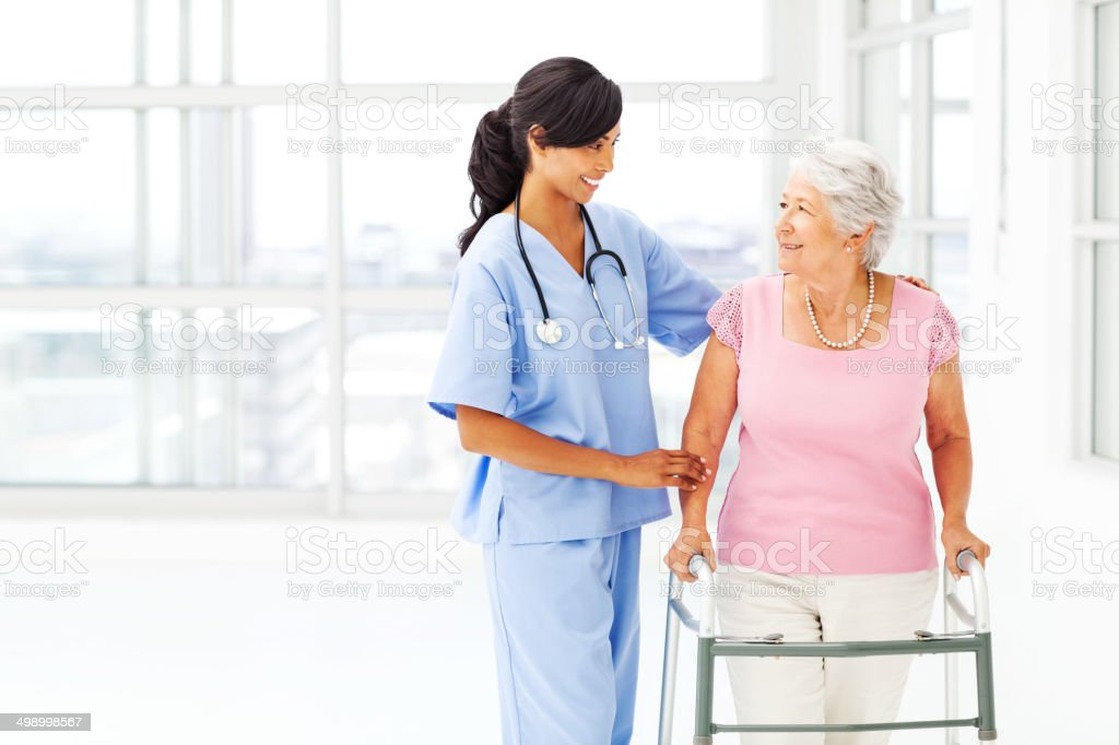 Nurse Helping Senior Woman With Walker While Looking At Her stock photo