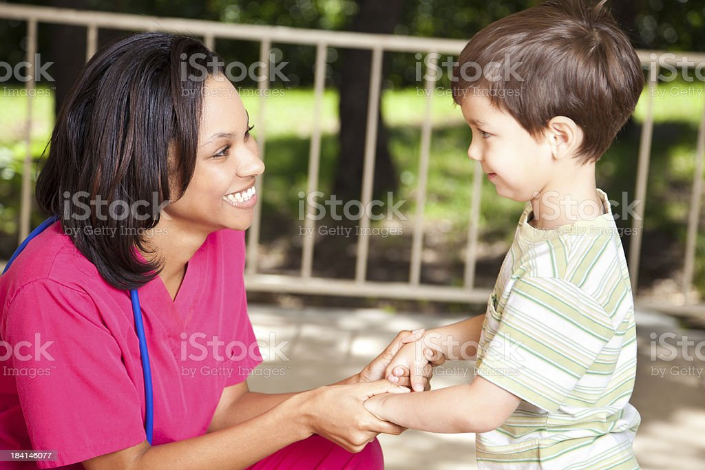 Nurse Helping Young Boy Outside stock photo