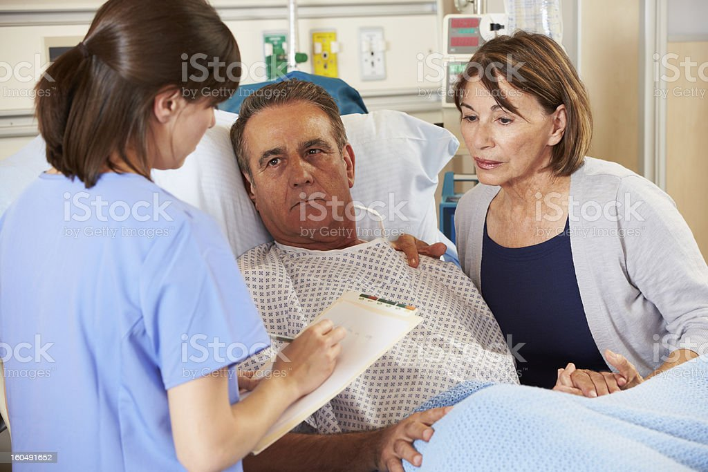 Nurse holding clipboard and talking to couple in hospital royalty-free stock photo