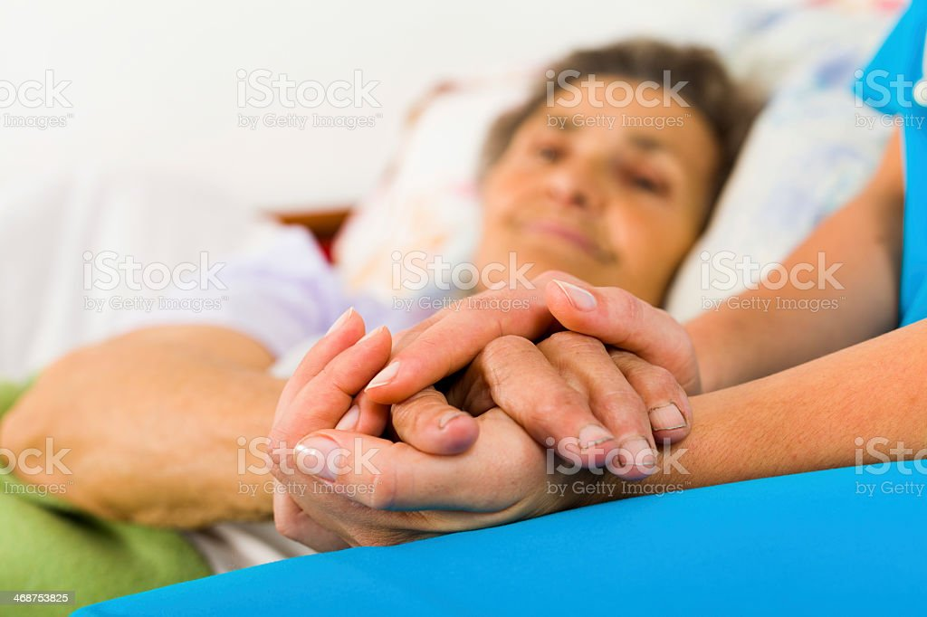 Nurse holding elderly patient's hand stock photo