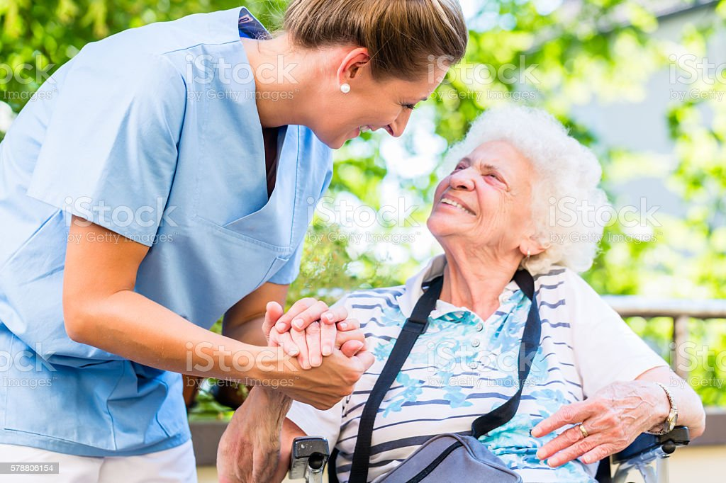 Nurse holding hand of senior woman in pension home stock photo