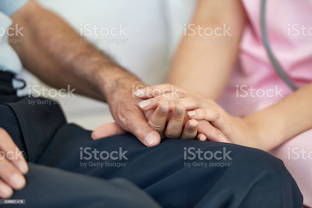 Close up of nurse holding hand of patient.