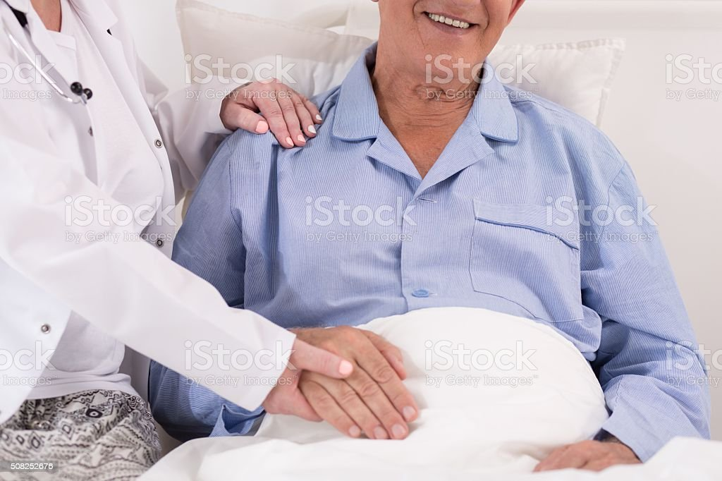 Nurse in white gown holding retired patient\'s hand