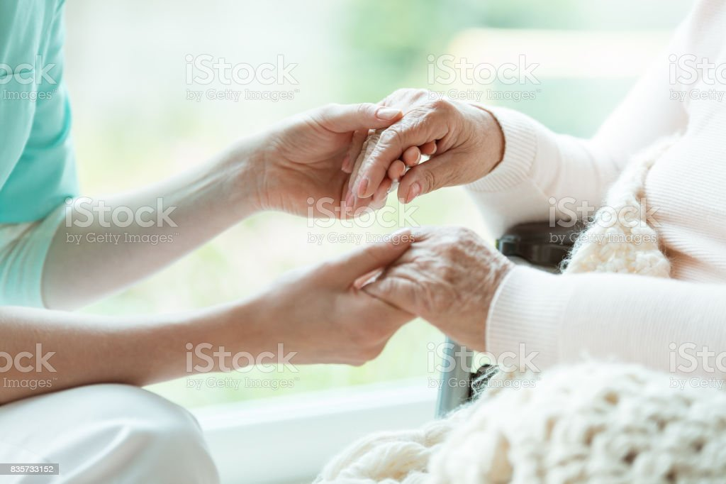 Photo of nurse holding her woman patient\'s hands with painted nails