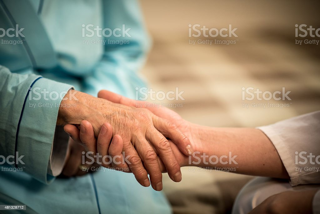 Nurse holding  senior woman's hand, close-up stock photo