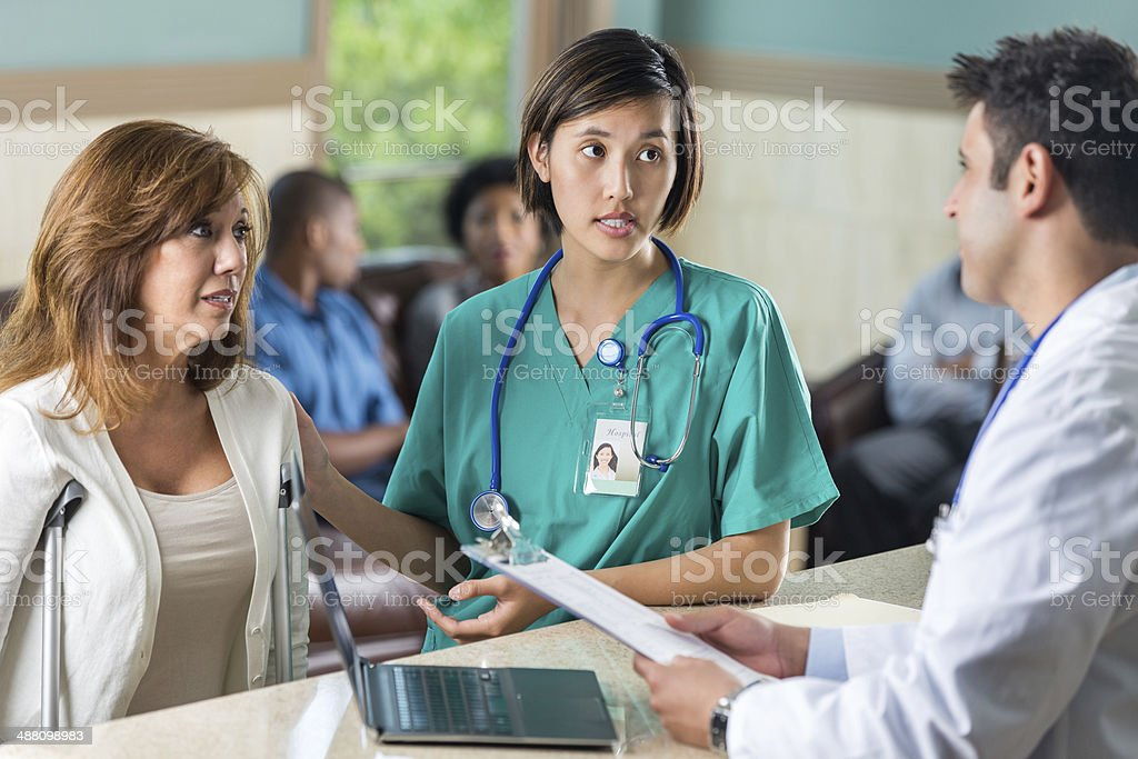 Nurse introducing injured patient to doctor in hospital waiting room stock photo