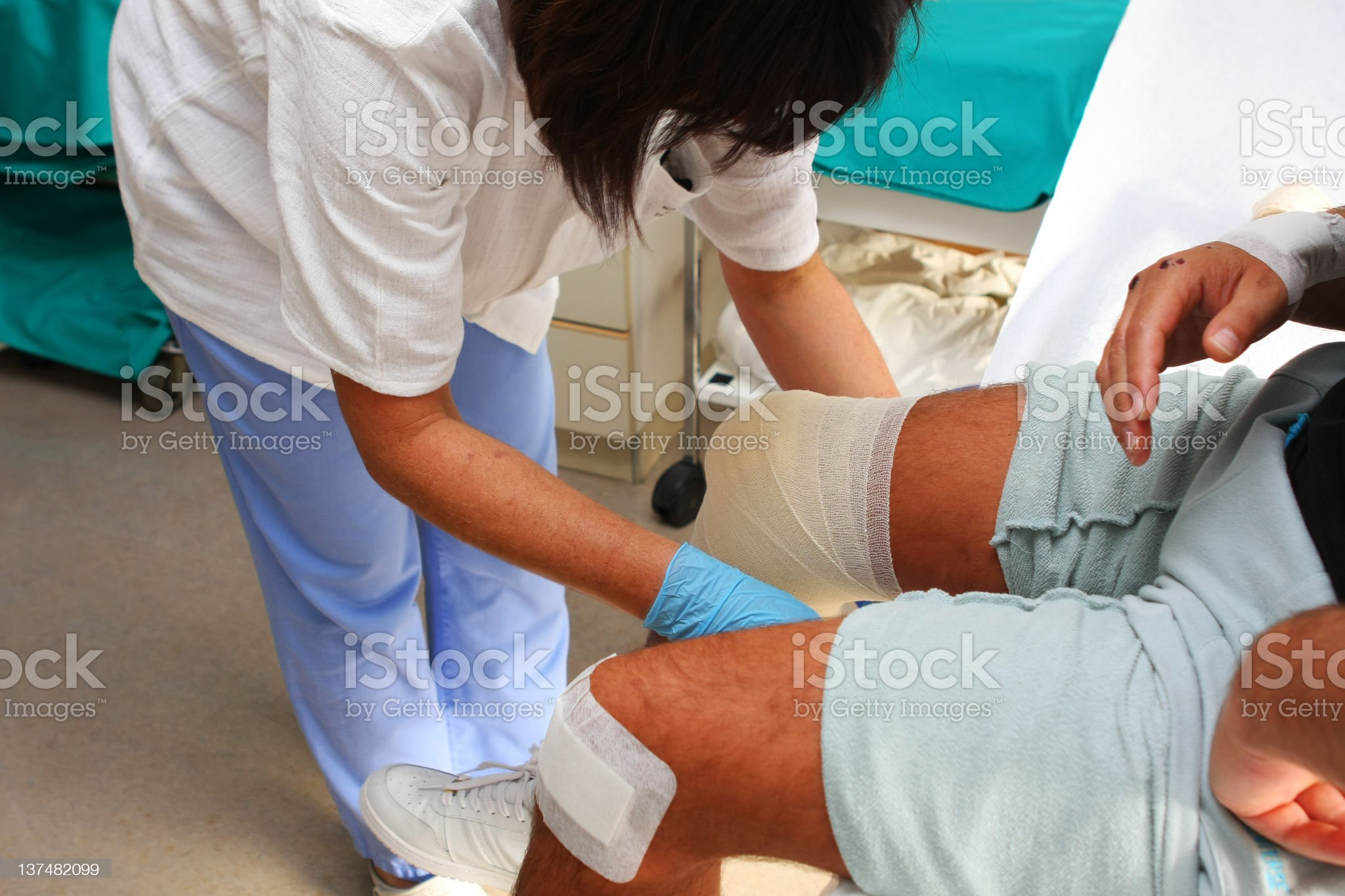 Nurse is taking care of the wounded knee,changing bandage royalty-free stock photo