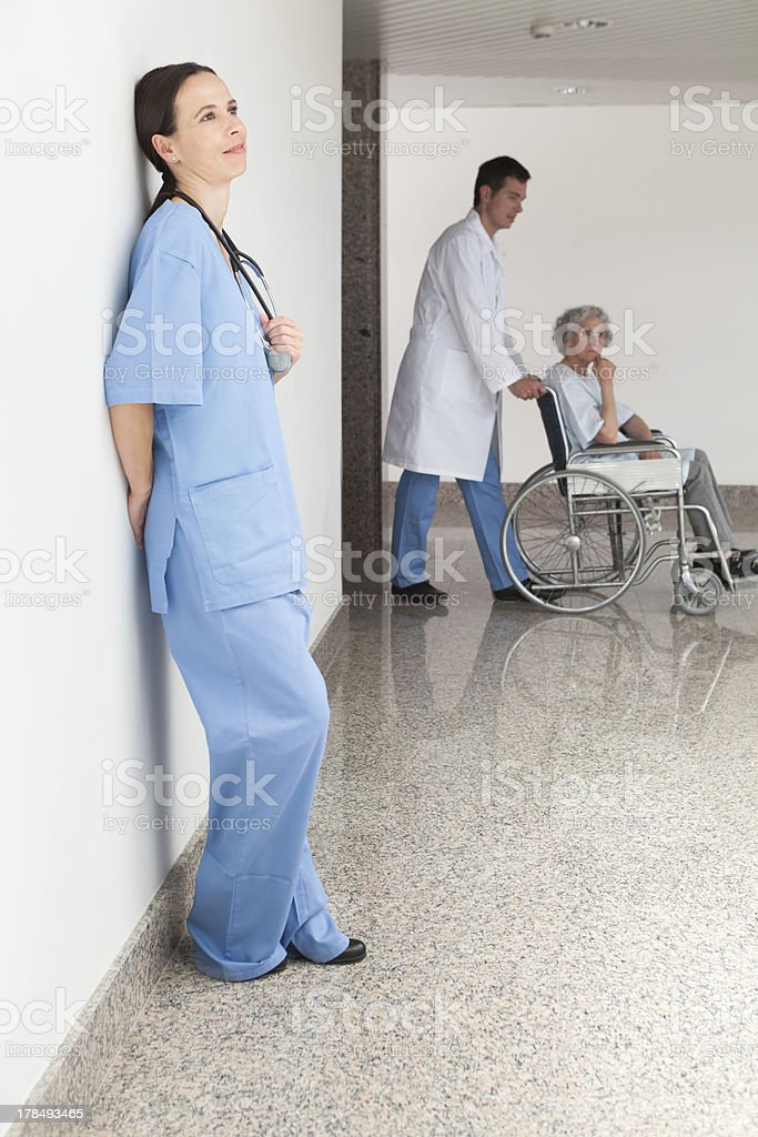 Nurse leaning against wall stock photo