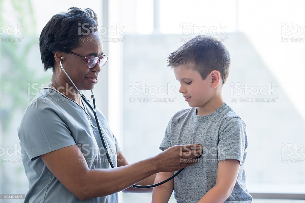 Nurse Listening to a Child's Heartbeat stock photo