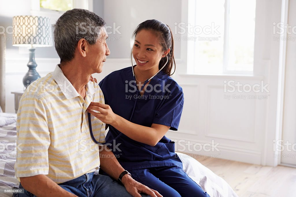Nurse Making Home Visit To Senior Man For Medical Exam stock photo