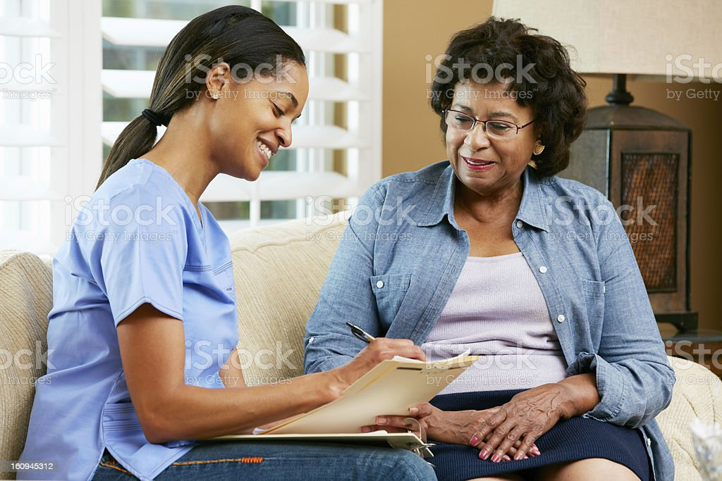 Nurse Making Notes During Home Visit With Senior Patient stock photo