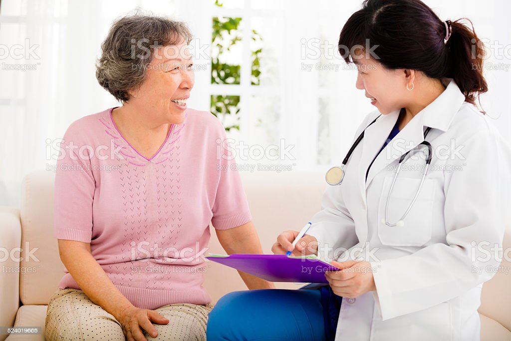 Nurse Making Notes During Home Visit With Senior woman stock photo