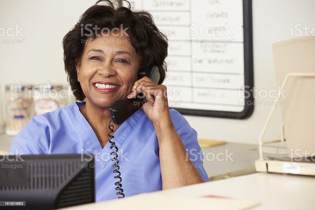 Nurse Making Phone Call At Nurses Station stock photo