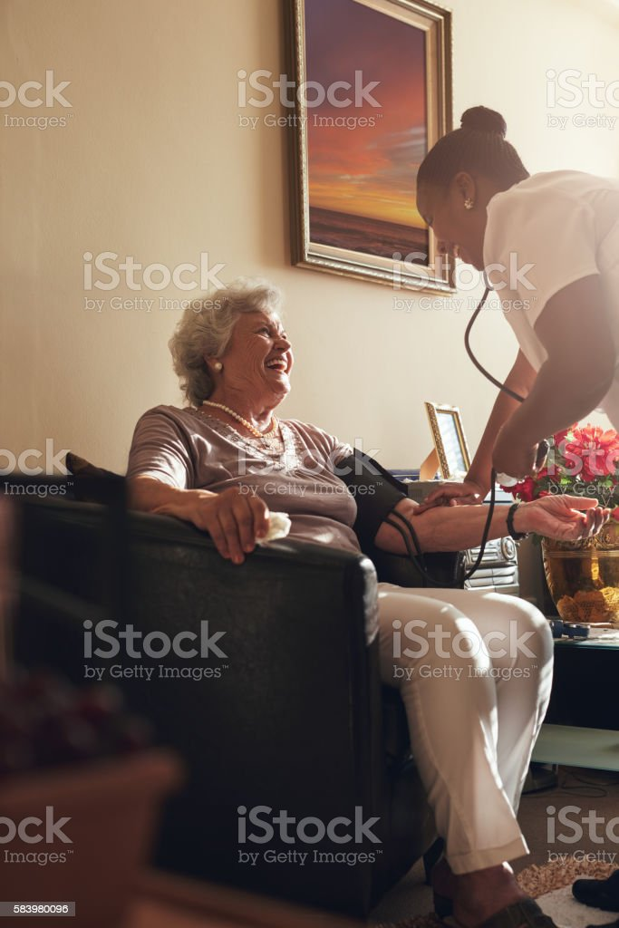 Nurse measuring blood pressure of senior lady patient stock photo