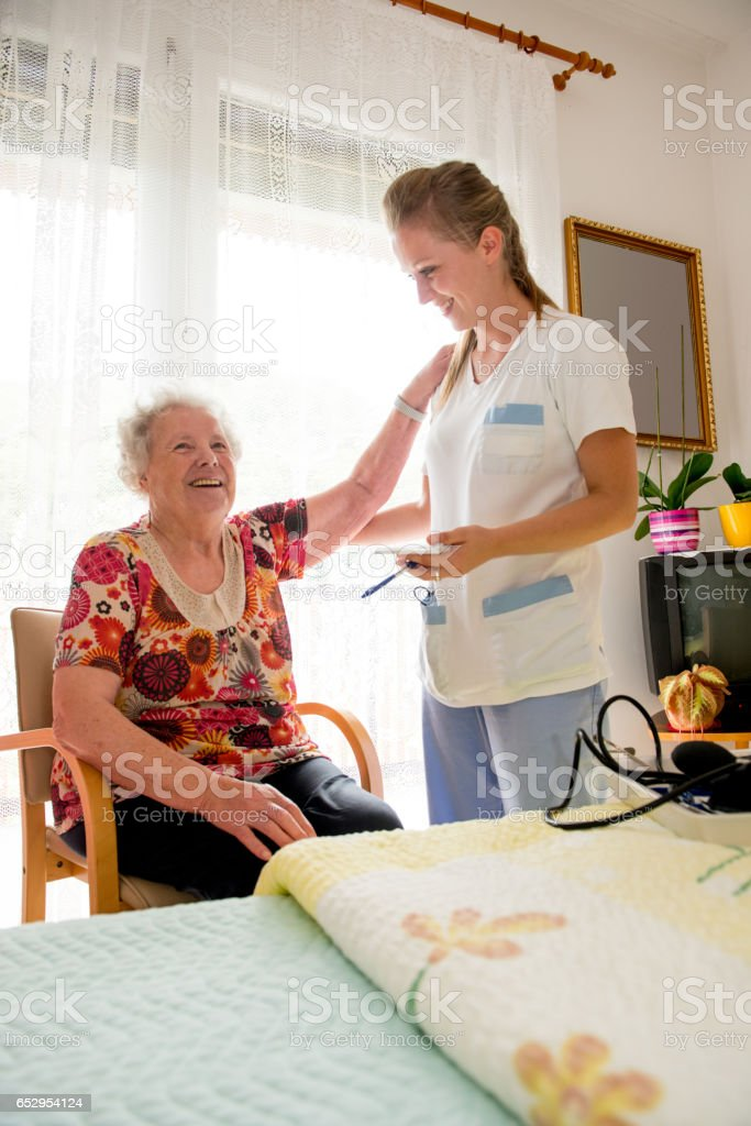 Nurse Measuring Blood Pressure To A Senior Woman In The Nursery Home stock photo
