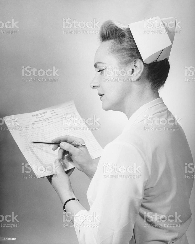 Nurse noting on patient's chart, (B&W) stock photo