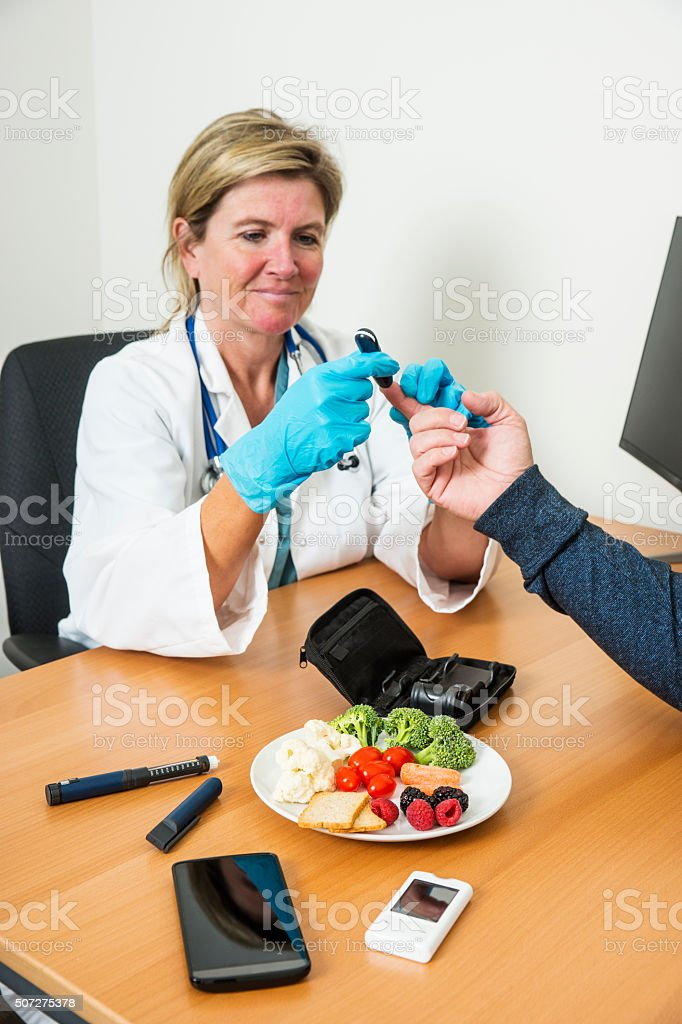 Nurse or doctor taking a blood sample from diabetic patient. stock photo