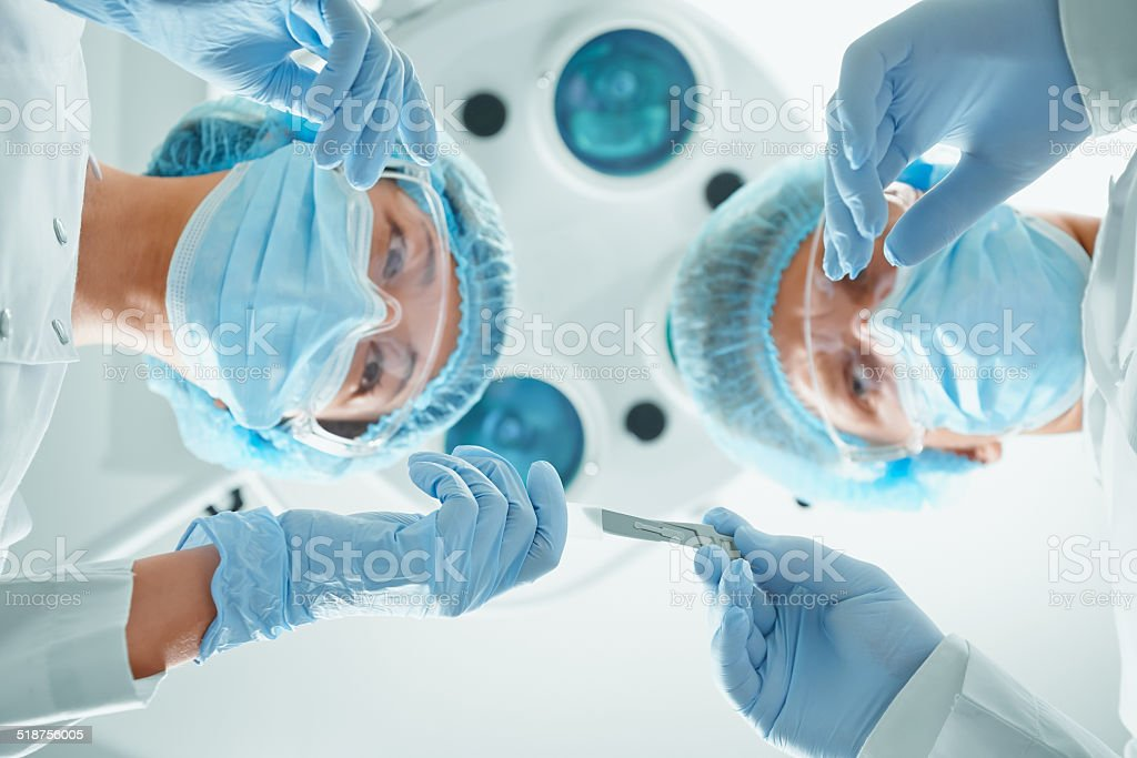 Nurse passes a scalpel to surgeon stock photo