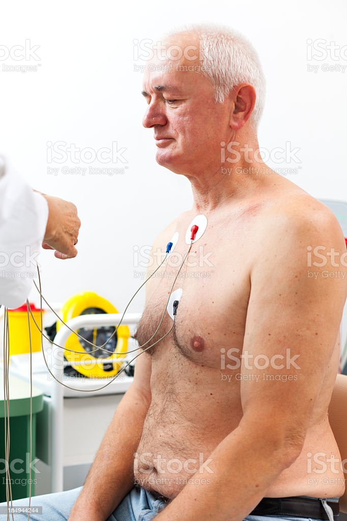 Nurse placing Holter monitor on patient's chest stock photo