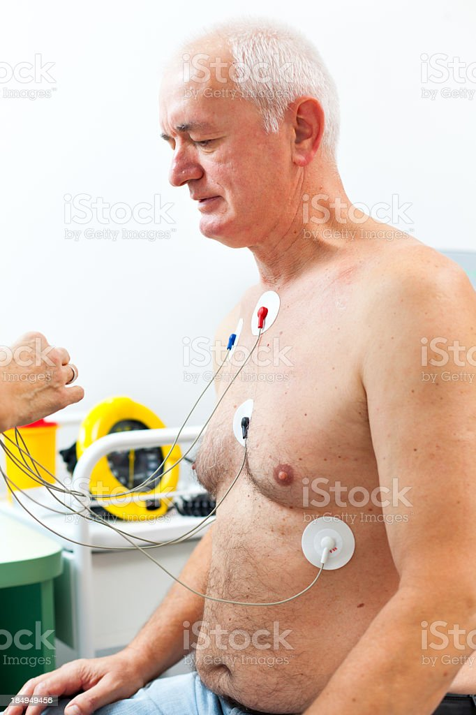 Nurse placing Holter monitor on patient's chest royalty-free stock photo