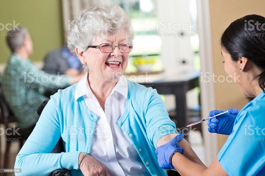 Nurse prepares to give senior patient an injection stock photo