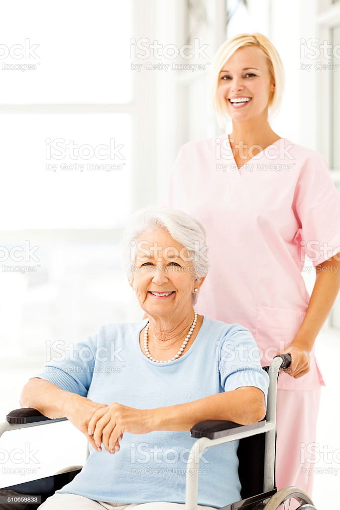 Portrait of happy nurse pushing female patient on wheelchair at...