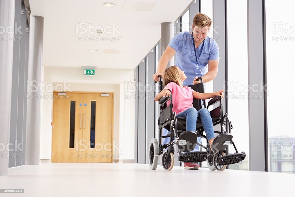 Nurse Pushing Girl In Wheelchair Along Corridor stock photo