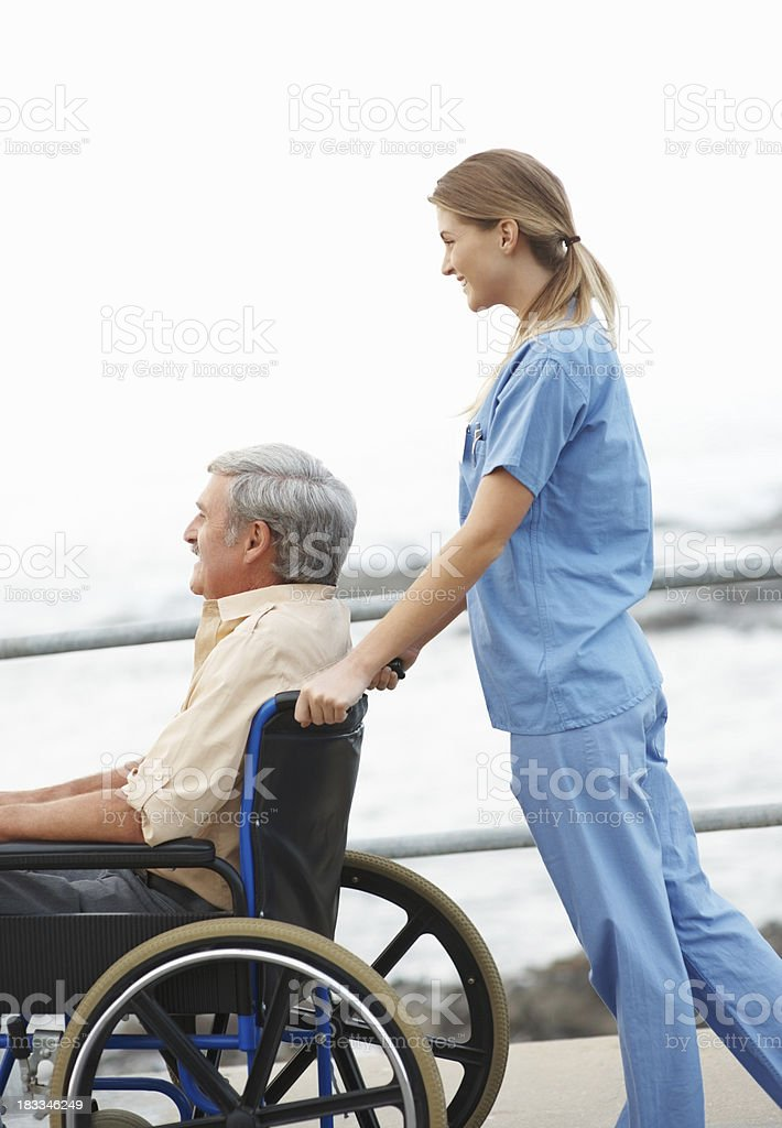 Nurse pushing man in a wheelchair - outside royalty-free stock photo