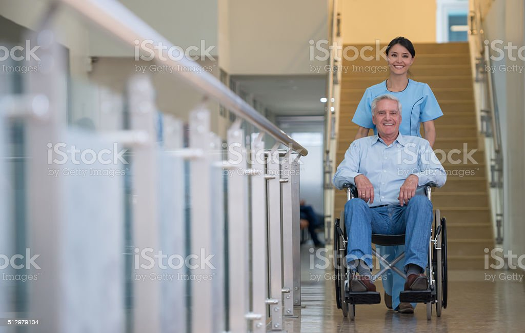 Nurse pushing patient in a wheelchair at the hospital stock photo
