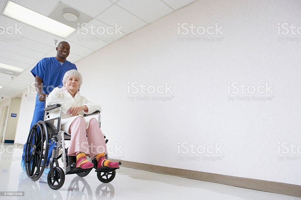 Nurse pushing patient in a wheelchair stock photo