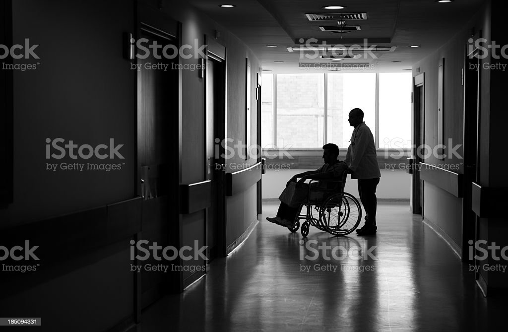 Nurse Pushing patient Sitting in Wheelchair in corridore stock photo