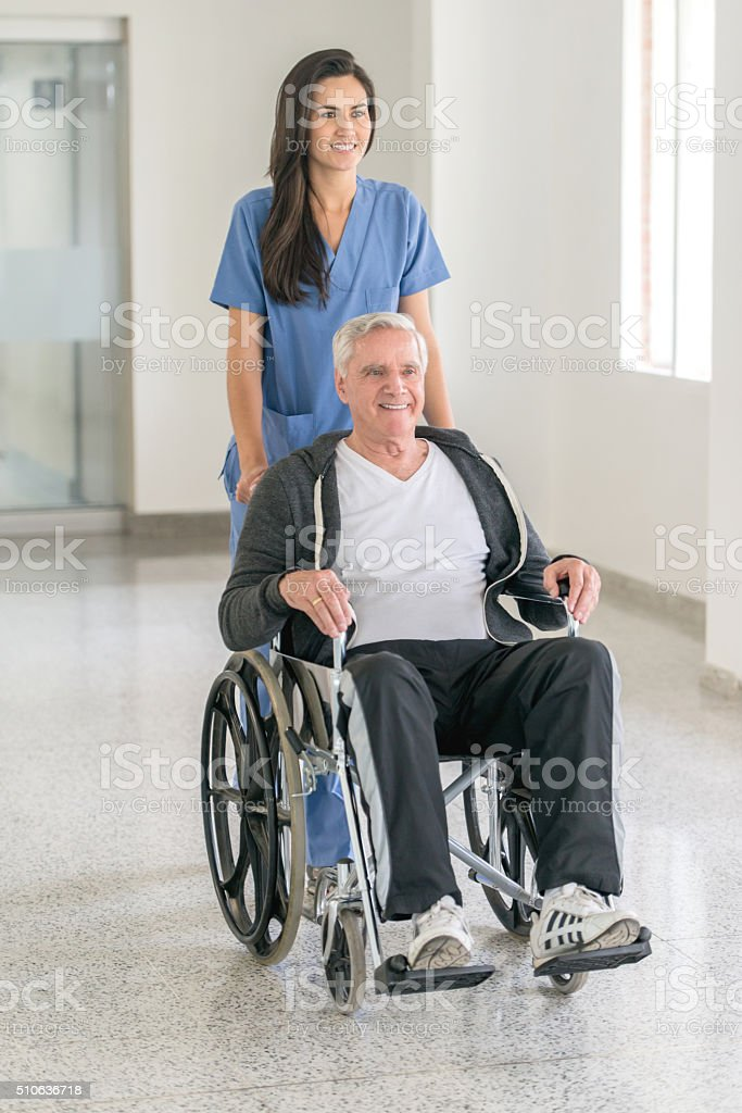 Nurse pushing senior male in a wheelchair at the hospital stock photo