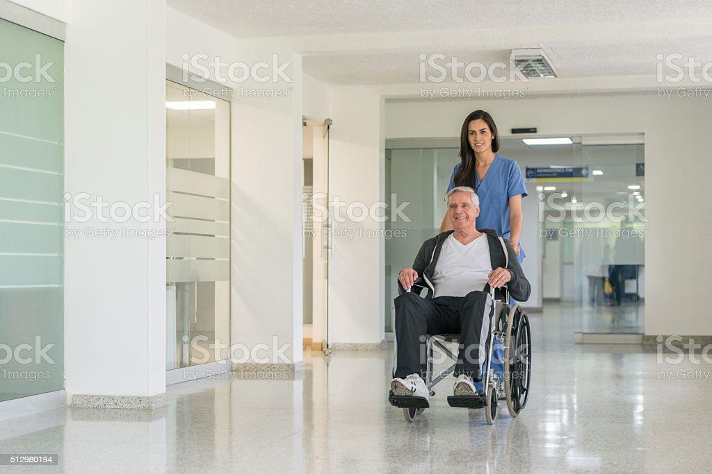 Nurse pushing senior man in a wheelchair stock photo